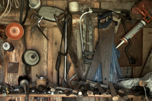 different old tools hanging on a barn wall